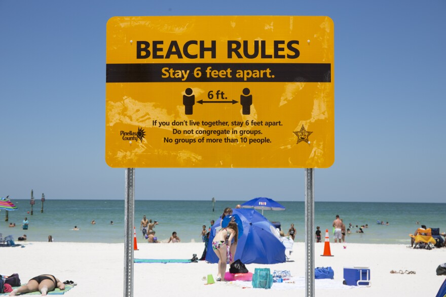 A yellow beach sign encourages people to stay six feet apart.
