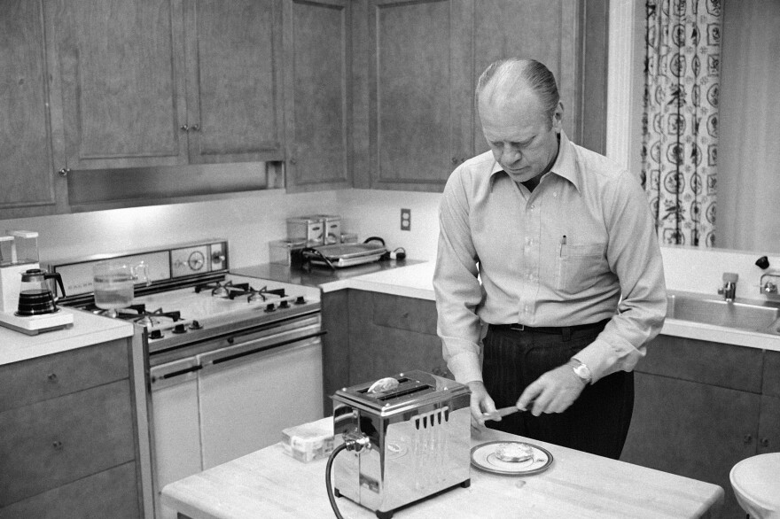 President Gerald Ford prepares English muffins, which he toasted in the kitchen of the family quarters at the White House, in 1974. Ford had always fixed his own breakfast and did not change the habit.