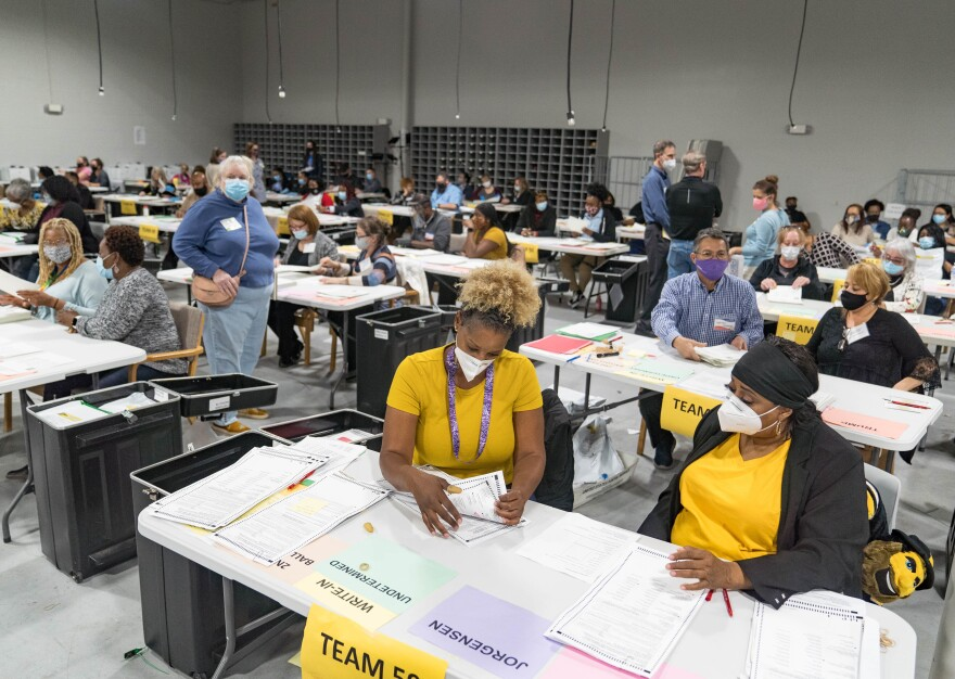 Gwinnett County election workers handle ballots on Nov. 16 as part of the recount for the 2020 presidential election.