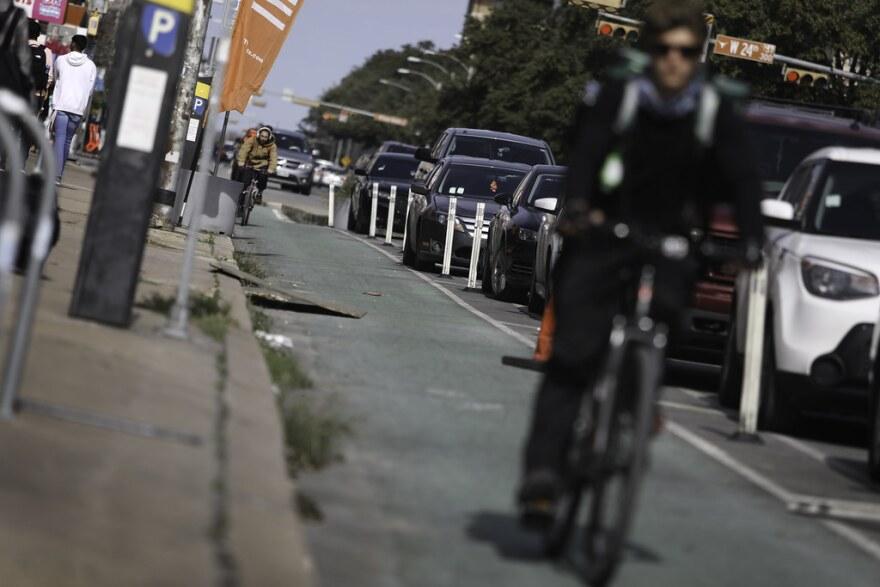 A biker rides in a bike lane down Guadalupe Street.