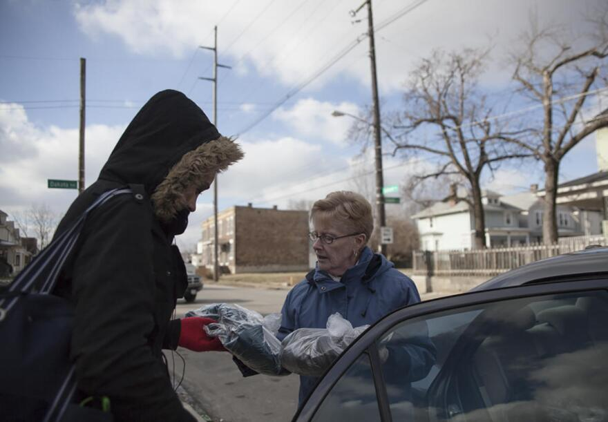 Sister Nadine hands out sack lunches to women in the Hilltop in Columbus, Ohio.
