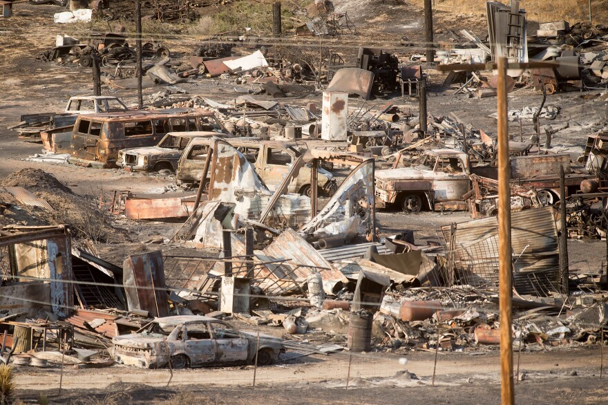 Scorched cars and trailers burned by the Blue Cut fire line a residential street in Phelan, Calif., on Friday.