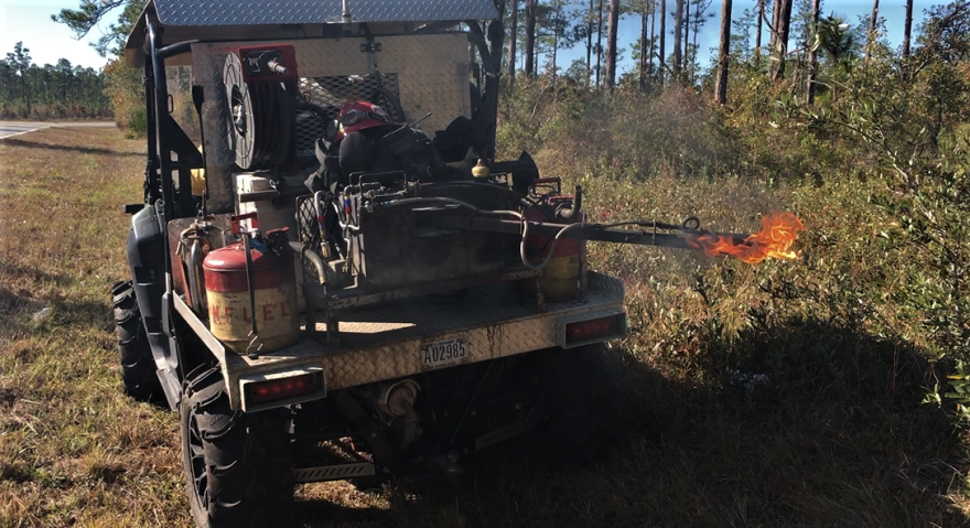 Vehicle with a mechanical arm spit fire out onto grass.