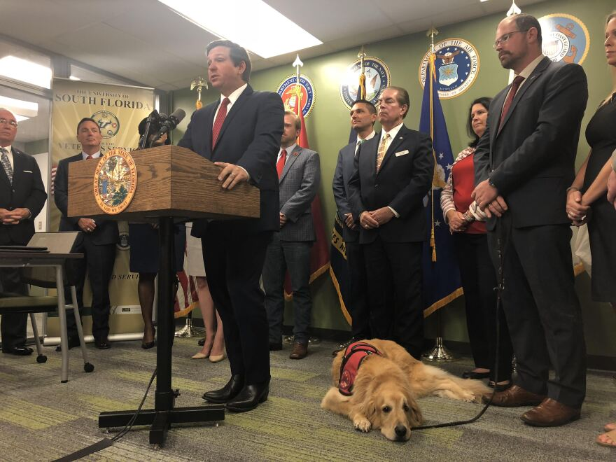 Surrounded by veterans, other officials and Hero the dog, Florida Governor Ron DeSantis speaks at the University of South Florida on Wednesday.