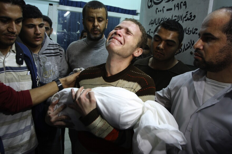 Jihad Masharawi weeps while he holds the body of his 11-month old son Ahmad, at Shifa hospital following an Israeli air strike on their family house, in Gaza City on Wednesday.