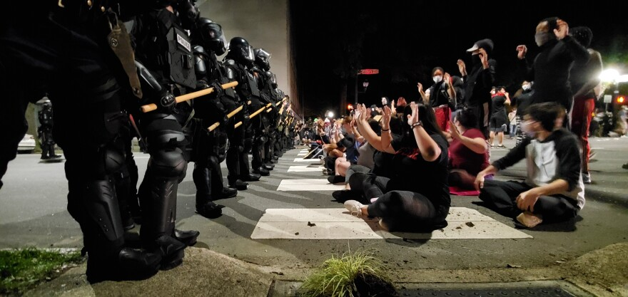 Protesters and police in riot gear face off at demonstrations on Sunday night in Raleigh.