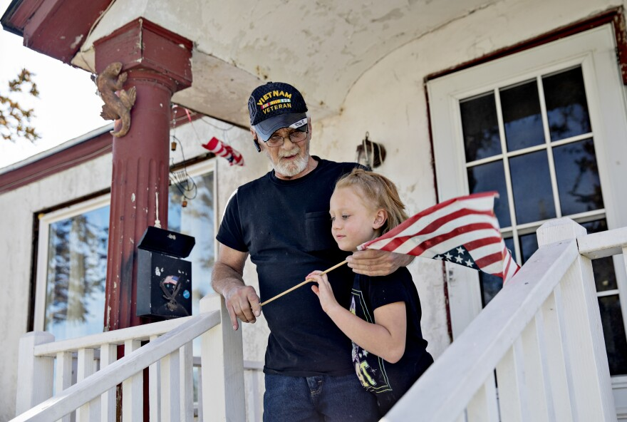 An older man and child stand on a porch holding an small American flag.