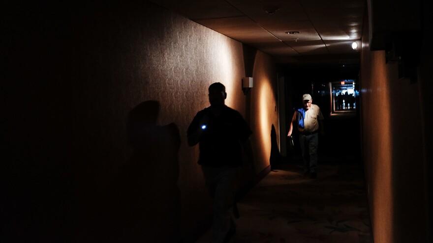Hotel guests walk through dark hallways in Fort Myers, Fla., on Sunday.