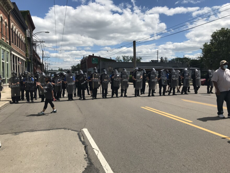 Police officers with shields slowly walked forward in a line ear the entrance to U.S. 35 while protesters turned around to walk in the other direction.