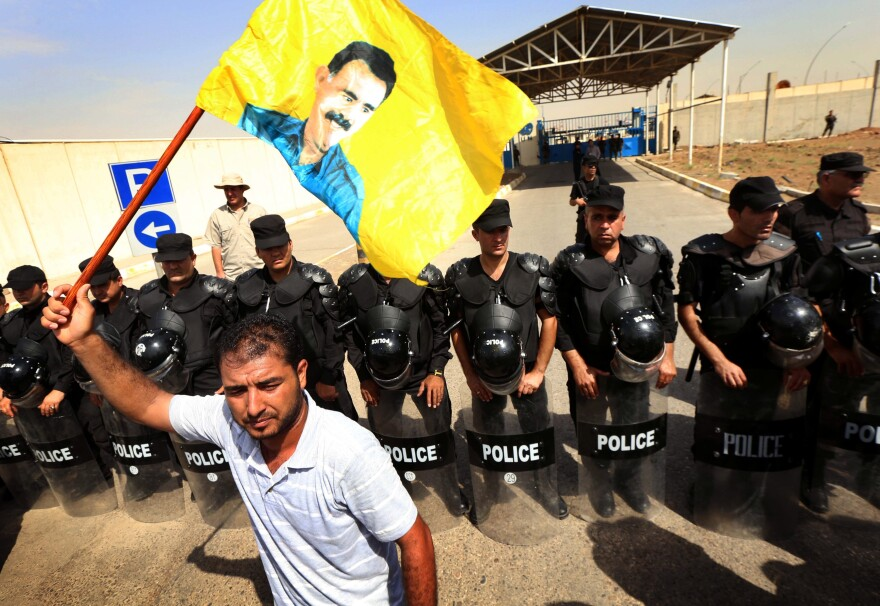 The U.S. has different policies toward different Kurdish groups. The U.S. works closely with Iraqi Kurds, whose policemen form a line in this photo. But the U.S. labels a militant Kurdish group from Turkey, the PKK, a terrorist organization. A PKK supporter waves a yellow flag of the group's leader. Three separate Kurdish militias have been fighting the group that calls itself the Islamic State.