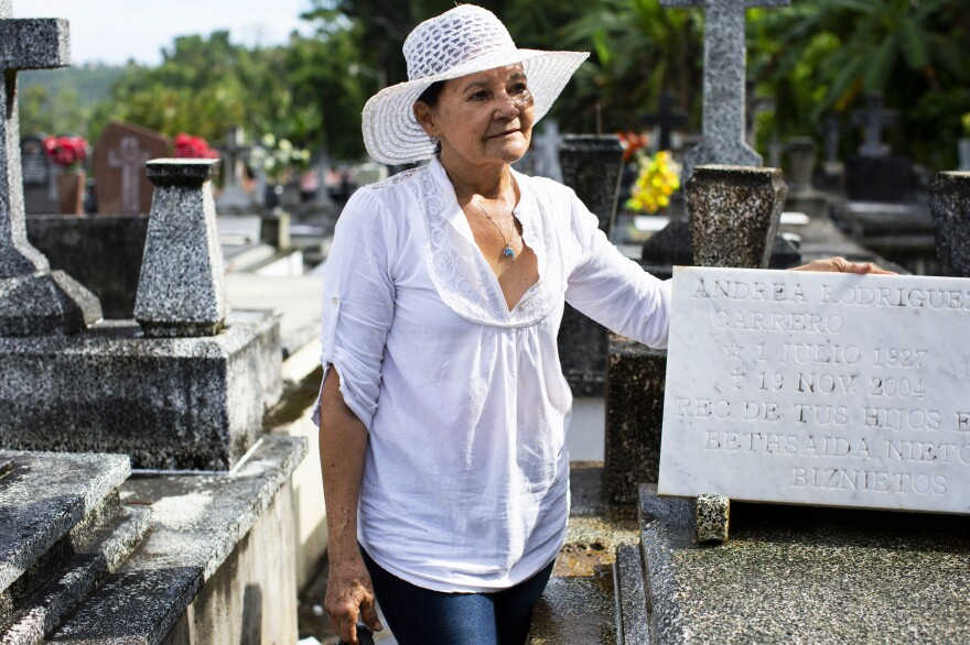"Bethsaida Román stands next to her mother's grave after entering the cemetery for the first time since Hurricane Maria. ""This is my Mother's Day gift,"" said Roman. She used to visit the grave at least twice a year and felt angst that so much time had gone by without being able to tend it."