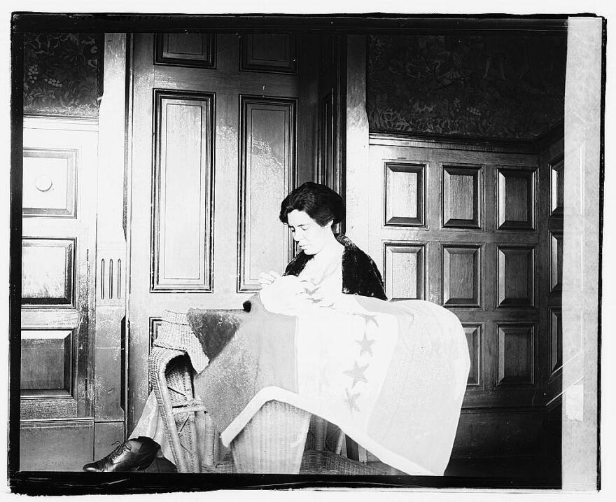 A photo of suffragette Alice Paul sewing a flag circa 1920.