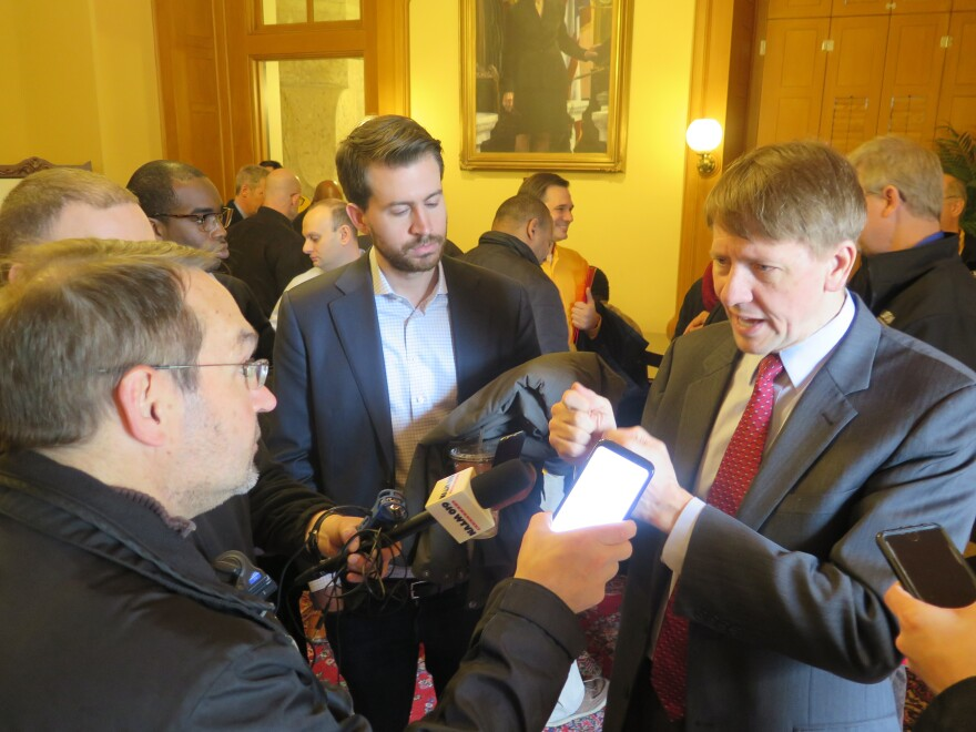 A photo of Cordray taking questions from reporters.