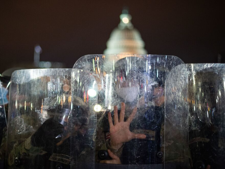 National Guard troops stand behind shields outside the Capitol building in Washington, D.C., on Wednesday evening.