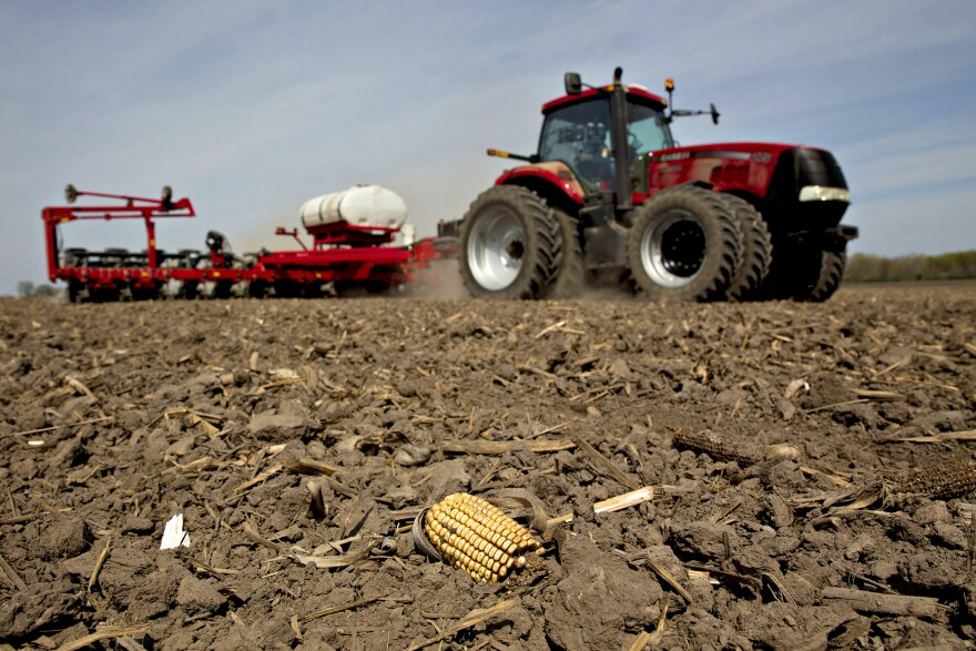 A tractor pulls a planter through a field as corn is planted in Princeton, Ill.