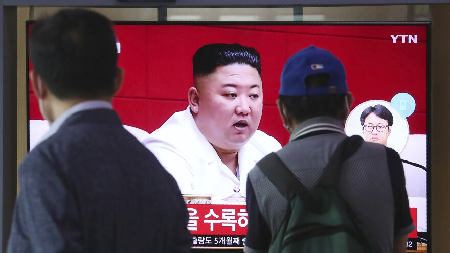 People at the Seoul Railway Station in Seoul watch a news program Friday showing a file image of North Korean leader Kim Jong Un, who said he was sorry over the killing of a South Korean fisheries official near the two countries' disputed sea boundary.