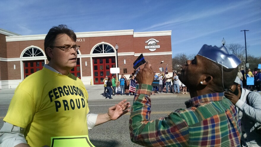 Police supporter Blake Ashey and protester Meldon Moffitt, both of Ferguson, exchange words across the street from the Ferguson Police Department.