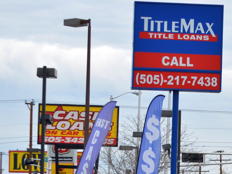 A photo that shows store signs for payday loan companies on busy street in Albuquerque, N.M.