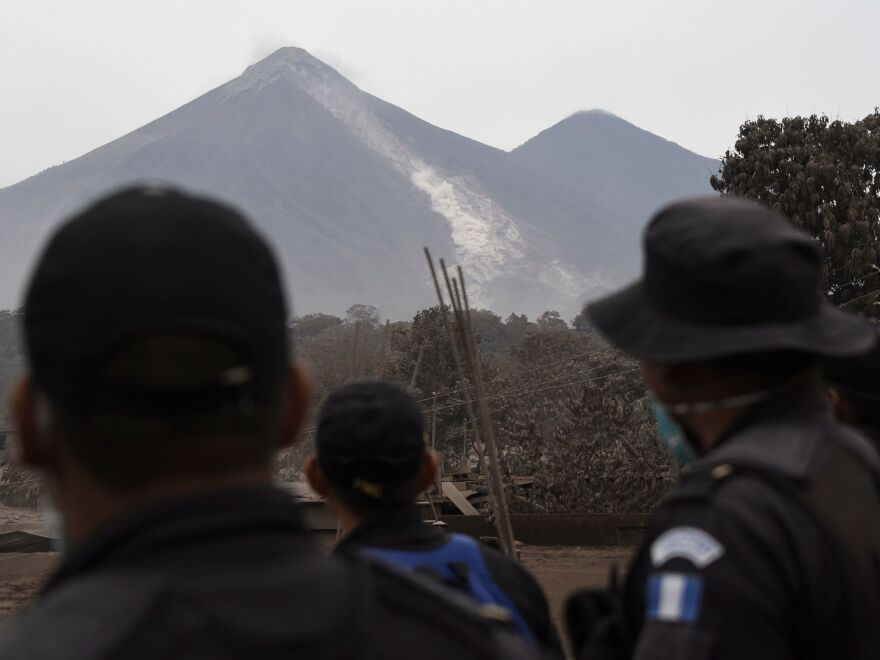 Police officers helping with the rescue efforts Monday look at the slope of the Fuego volcano from San Miguel Los Lotes. Evidence of the pyroclastic flow lingers on Mount Fuego's side, where the accumulated ash and rock have left bright gray scars from the eruption.
