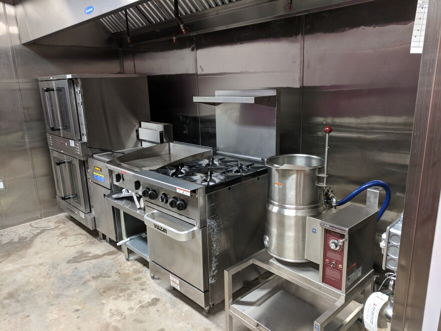 Silver ovens, stoves and kitchen utensils in an industrial kithcen