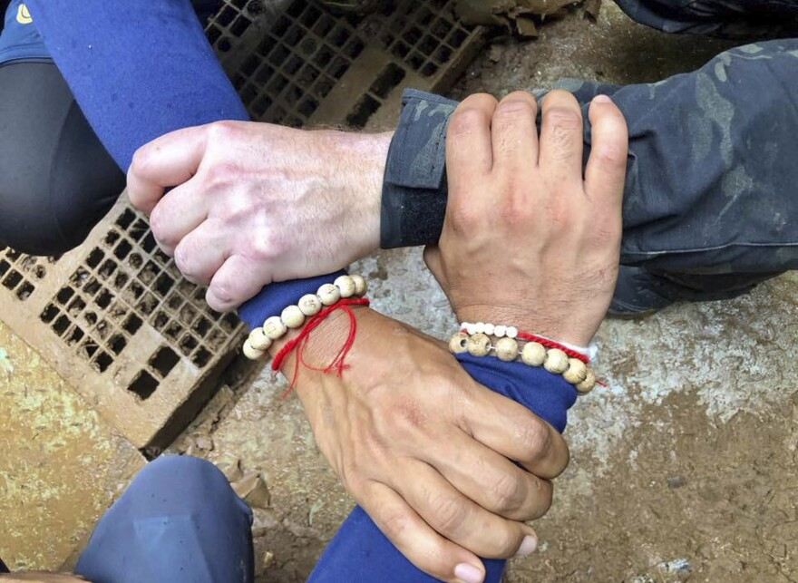 A photo released by the Thailand Navy SEAL Facebook page shows rescuers locking hands. Its caption says Thai and international rescuers are vowing to bring the boys home.