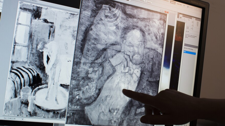 Scientists and art experts found a hidden painting beneath one of Picasso's first masterpieces, <em>The Blue Room,</em> thanks to advances in infrared technology. Here, associate conservator Patricia Favero of The Phillips Collection points to a detail in the image.