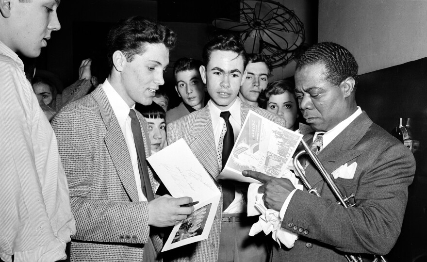 Jazz trumpeter Louis Armstrong signs autographs in the Blue Note nightclub in Chicago in 1948.