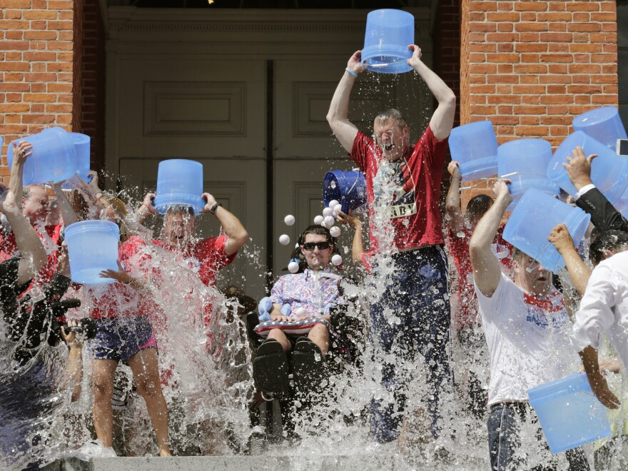Pete Frates, (seated, center) participates in the Ice Bucket Challenge with Massachusetts Gov. Charlie Baker to raise money for ALS research at the Statehouse in Boston in 2015.
