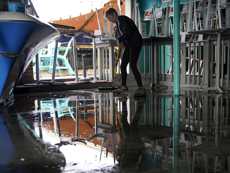 Kate Connell sweeps water and mud from the floor at Salty's Gulfport bar and in the aftermath of Tropical Storm Eta on Thursday in Gulfport, Fla.