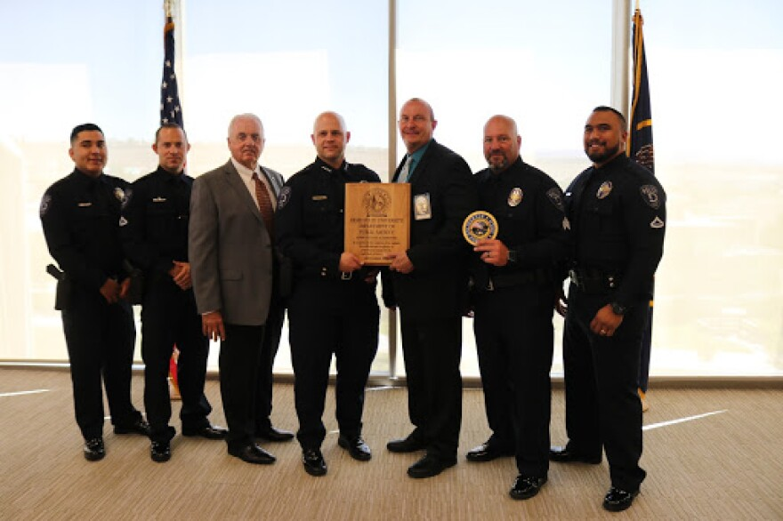 A group of police officers stand with a wooden plaque.
