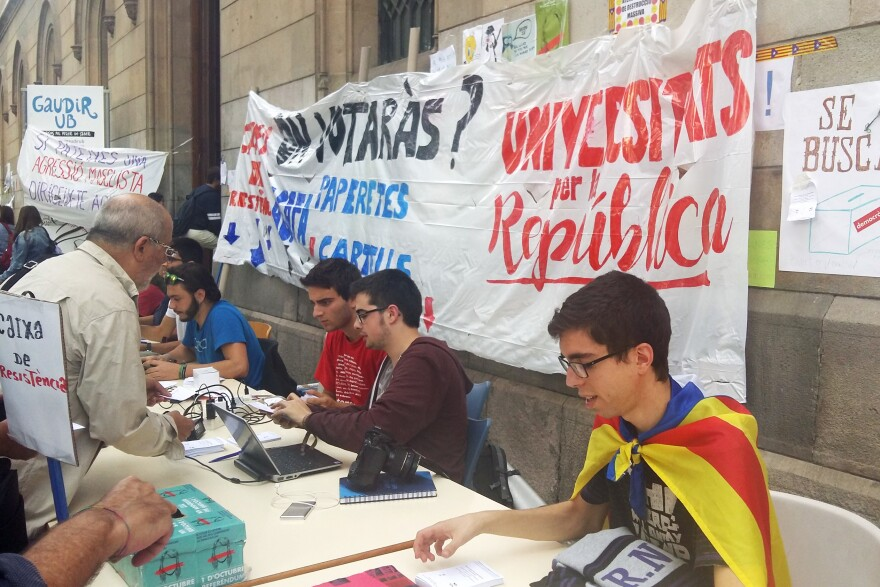 Students wear Catalan independence flags and hand out ballots in front of the University of Barcelona. Hundreds have been camping out at the university nightly ahead of Sunday's independence vote.
