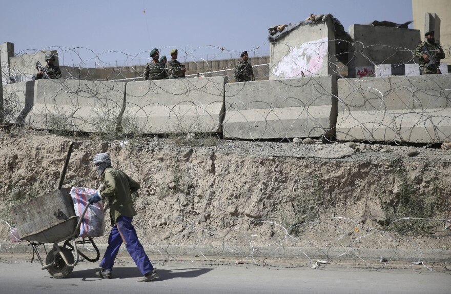 An Afghan laborer walks past a gate of Camp Qargha as Afghanistan National Army soldiers stand guard, west of Kabul, Afghanistan on Tuesday.
