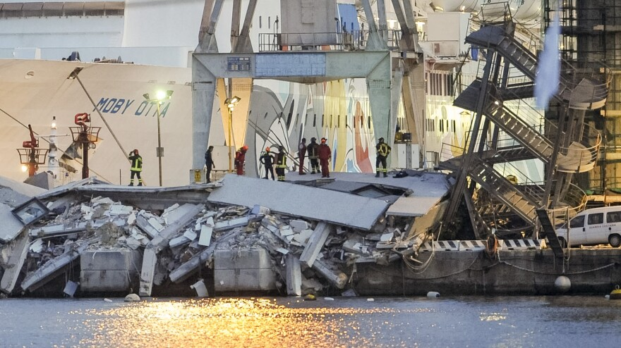 Rescuers search what is left of the control tower of the port of Genoa, northern Italy, on Tuesday.
