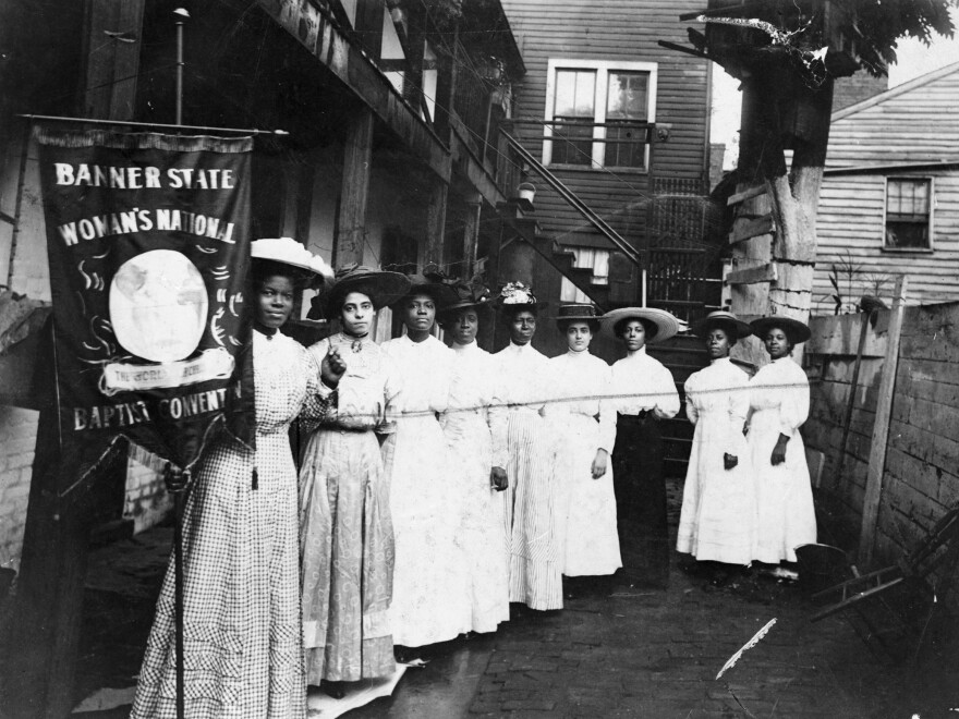 "Nannie Helen Burroughs holds a banner reading, ""Banner State Woman's National Baptist Convention"" as she stands with other African American women, photographed between 1905 and 1915. Burroughs was an educator and activist who advocated for greater civil rights for African Americans and women."