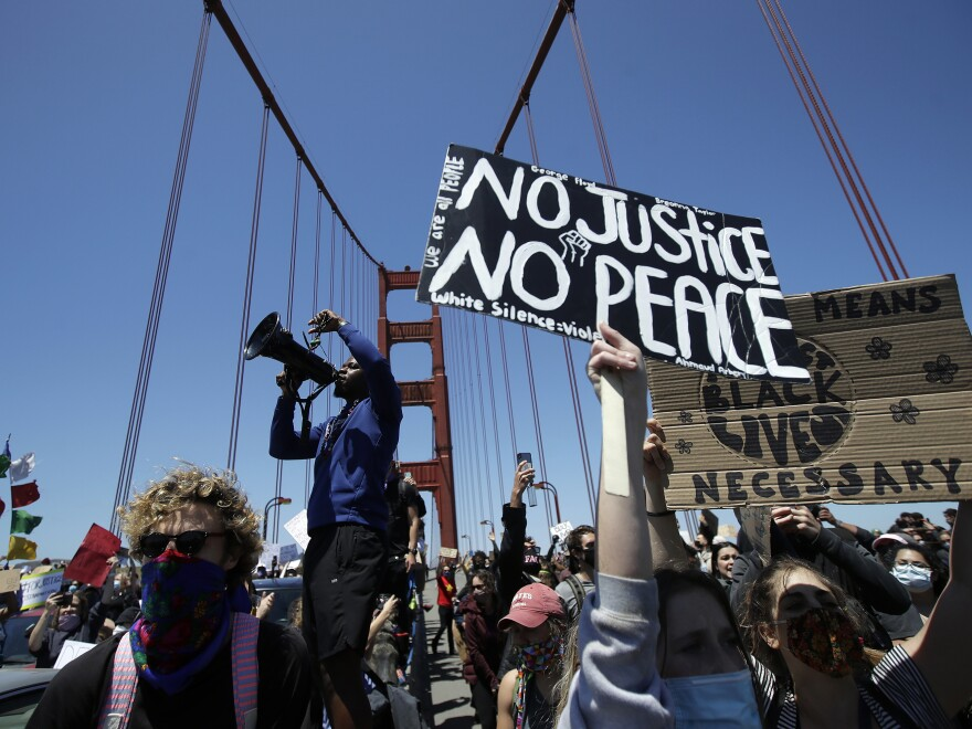 A man speaks into a megaphone while standing with others on the center divider as traffic is stopped on the Golden Gate Bridge in San Francisco Saturday.