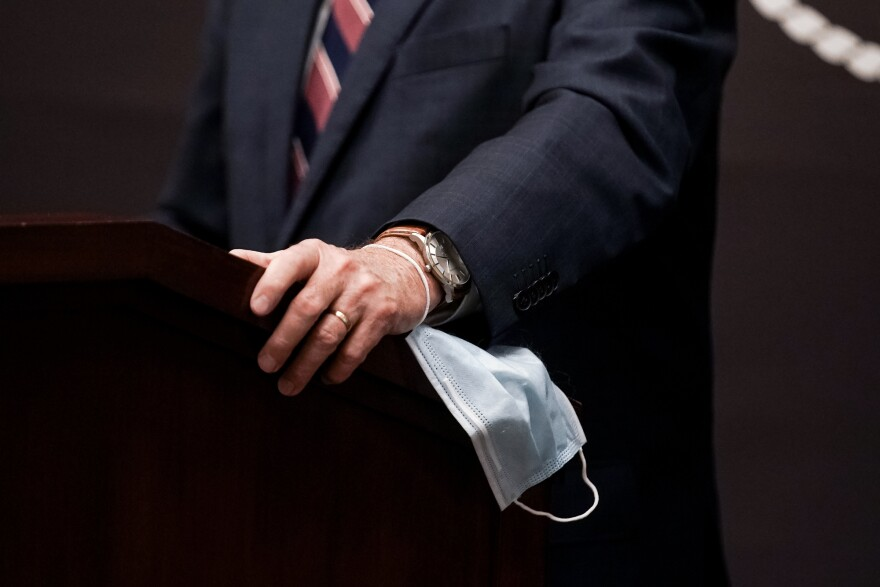 Photo of a hand on a podium with a mask.