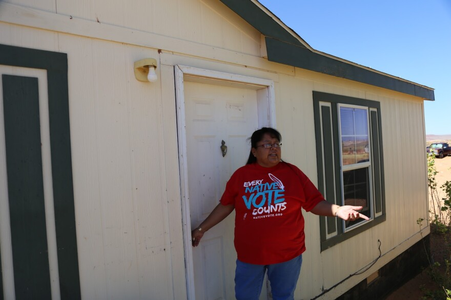 """Photo of woman in t-shirt that says """"every native vote counts"""" stands by door."""