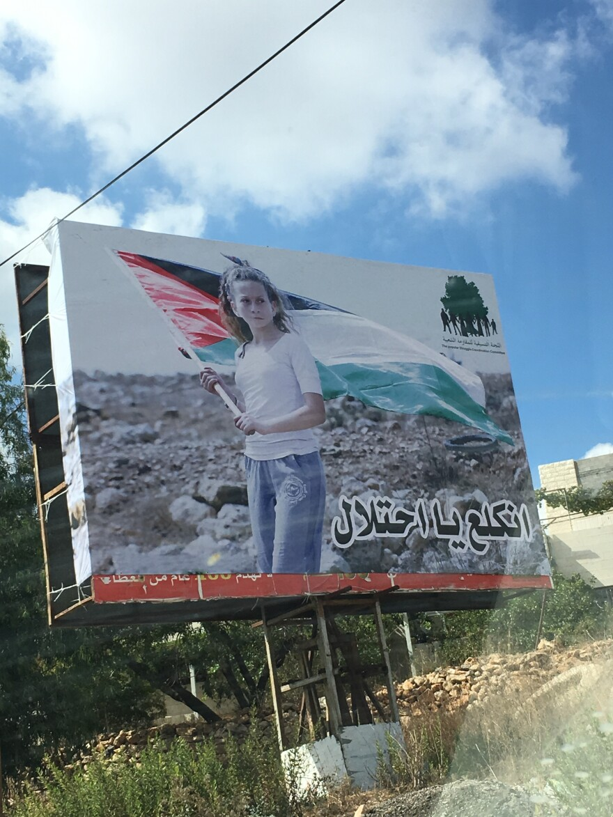 """Tamimi has become an icon for many Palestinians. A billboard in Nabi Saleh shows her photo with the words """"Go away occupation."""""""
