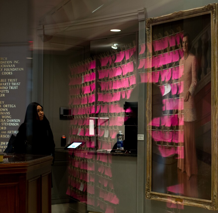 A reflection of pink index cards that are part of the Clothesline Project at the National Museum of Women in the Arts.