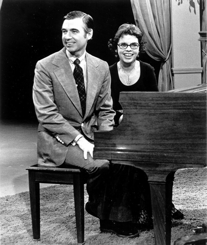 A picture of Fred and Joanne Rogers sitting at a piano.