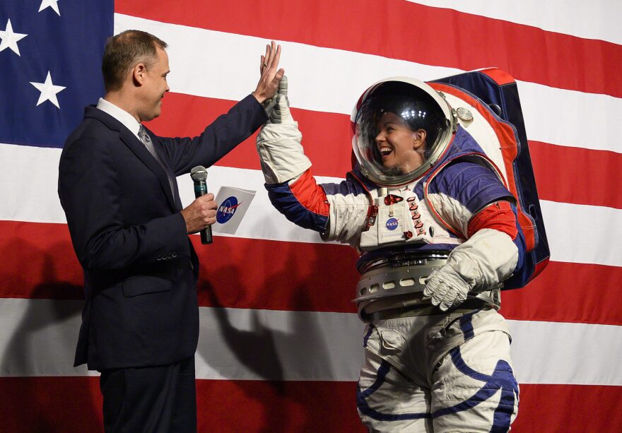 NASA administrator Jim Bridenstine (L) welcomes Advance space suit engineer, Kristine Davis (R), to the stage during a press conference displaying the next generation of space suits as parts of the Artemis program in Washington, DC.