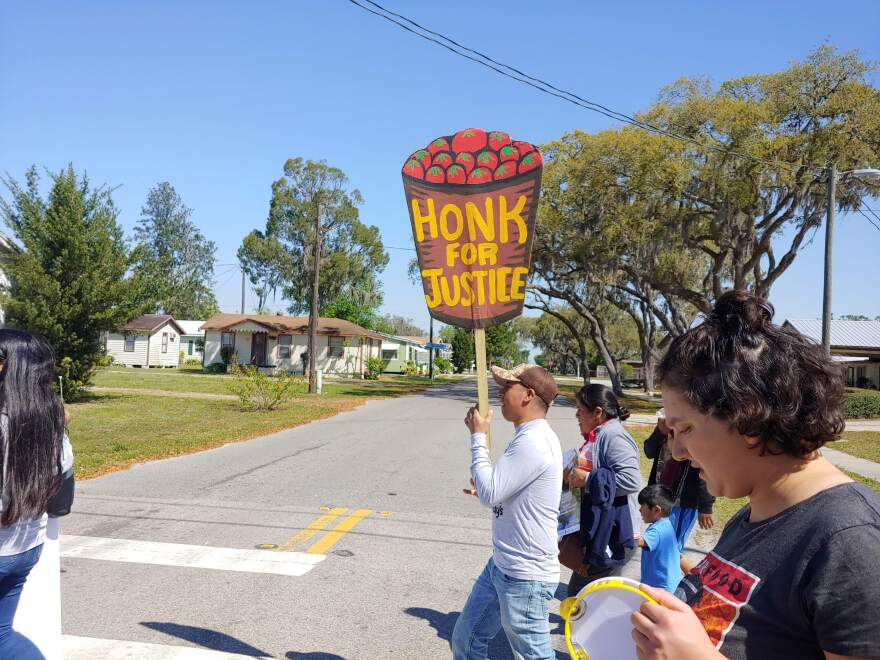"A marcher holds a sign that reads, ""Honk for Justice,"" at the Women's March in Wimauma, Florida."