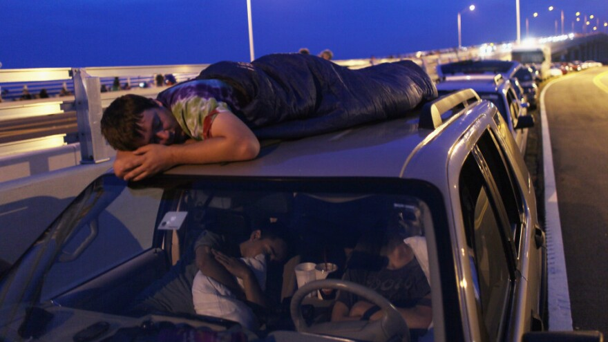 Spur King from Armarillo, Texas, slept on the roof of a van in Titusville, Fla., as he waited earlier today for, he hopes, the launch of Atlantis.
