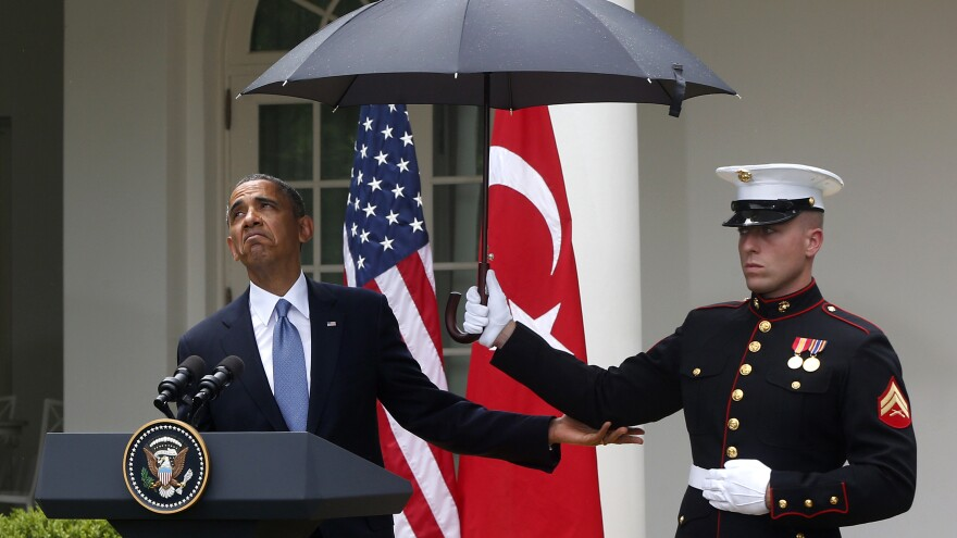 President Obama checks to see if it's still raining as a Marine holds an umbrella for him during a joint news conference with Turkish Prime Minister Recep Tayyip Erdogan at the White House on Thursday.