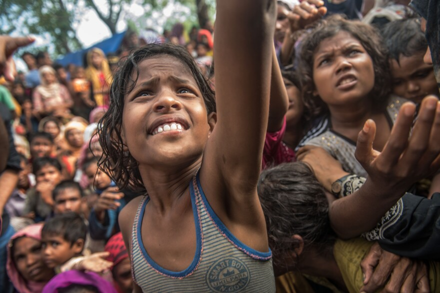 Girls reach out for food handed out by a volunteer organization in the Kutupalong refugee camp in Bangladesh.