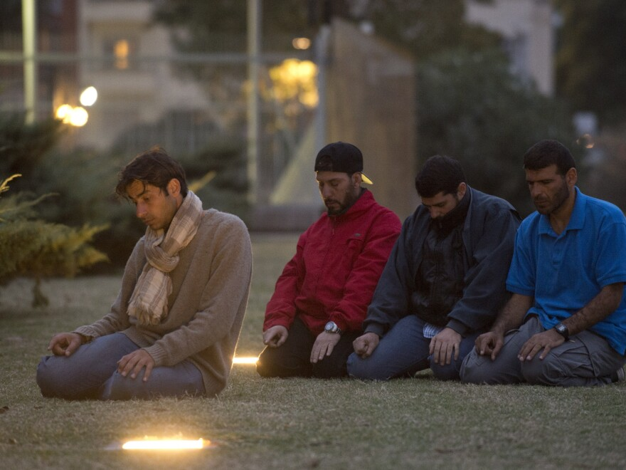 Former Guantanamo prison inmates (from left) Syrian Ahmed Adnan Ahjam, Tunisian Abdul Bin Mohammed Bin Abess Ourgy and Syrians Abdelhadi Omar Faraj and Ali Husein Shaaban pray in front of the U.S. Embassy in Montevideo on Wednesday.