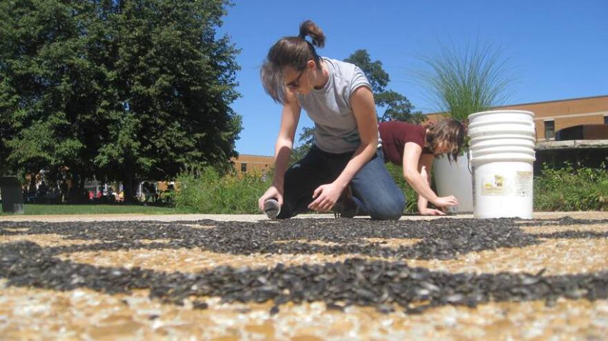 A participant helps with Jessica Witte's August 2015 project on the Schmidt Art Center patio in Belleville.