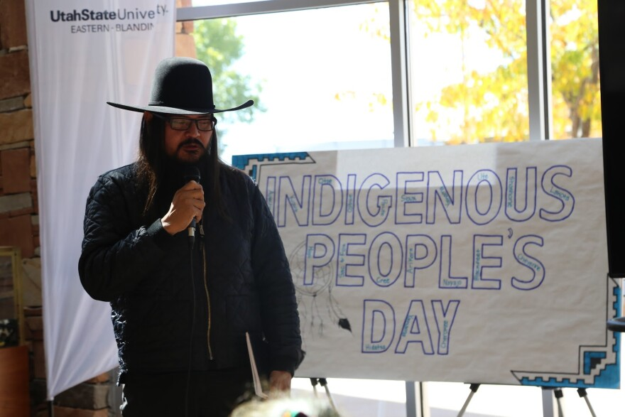 """Photo of a Navajo man wearing a black cowboy hat stands in front of a sign that says """"Indigenous People's Day."""""""