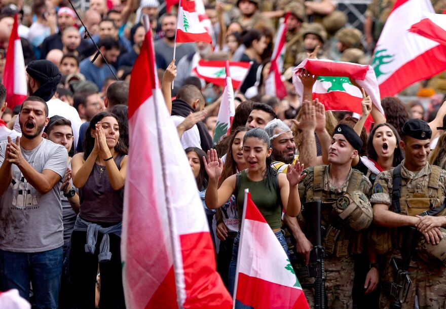 Anti-government protesters wave national flags as Lebanese army soldiers form a human barrier in the area of Jal el-Dib in the northern outskirts of the Lebanese capital of Beirut.