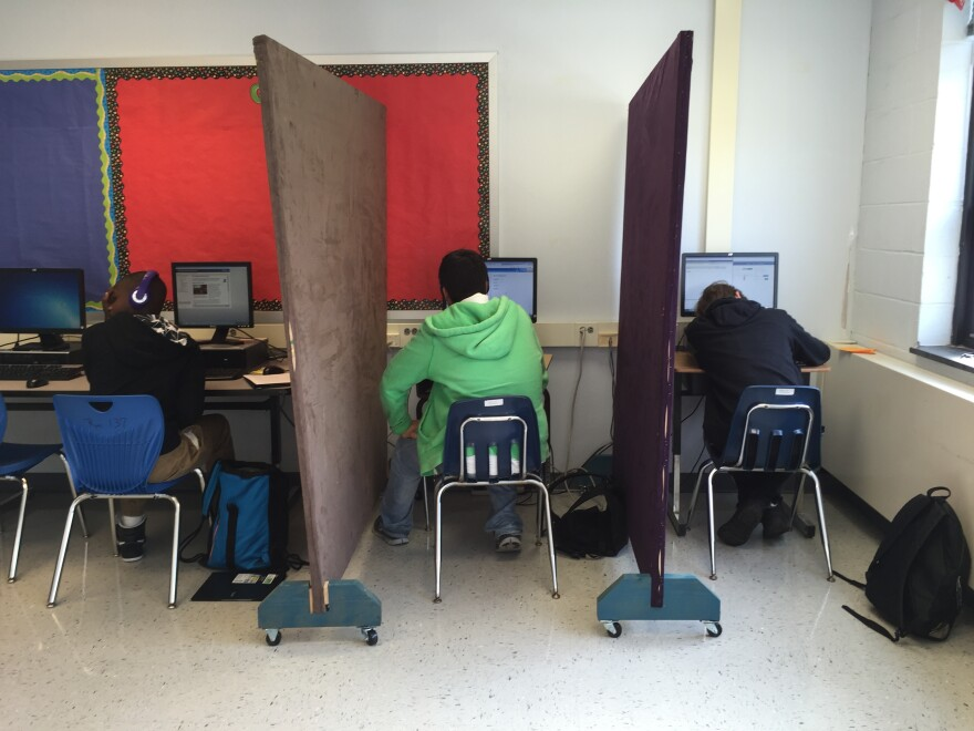 Students in the Aspire program work individually at computers separated by privacy screens. The partitions help the students feel less anxious.